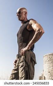 Muscled man in khaki pants and tank top perforated black, outdoor portrait.