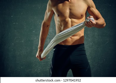 A muscled man with a naked body in black sweatpants is holding towels in his hands against a gray background