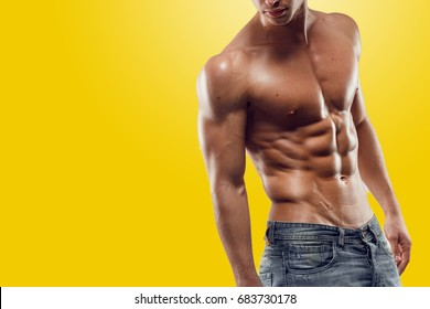Muscled man posing in studio, isolated on yellow background. Copy space. Horizontal view.