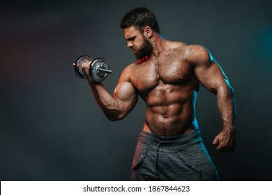 Muscled shirtless man with dumbbell doing his biceps exercise. Male body in colourful lightning in studio. Big hunk with six pack abs exercises in studio at grey background.