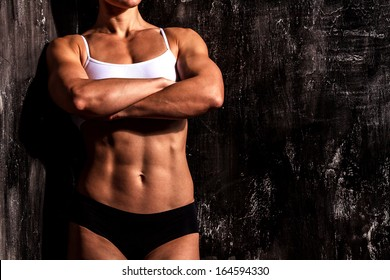 Muscled woman against the scratched grunge background