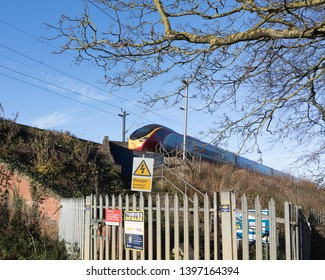 Muscott, Northamptonshire / UK - November 24th 2017: A London bound Virgin Pendolino on an embankment passes railings and warning signs on the side of the railway.