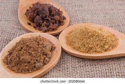 Muscovado sugar, brown sugar and coconut sugar n wooden spoon on gunny sack