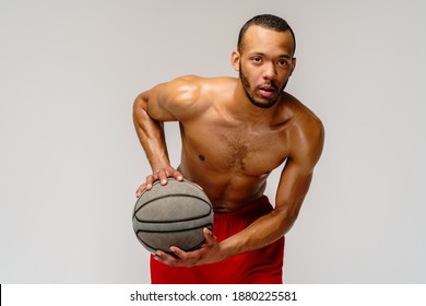Muskulär afrikanischer Sportler, der Basketball ohne Schatten auf hellgrauem Hintergrund spielt