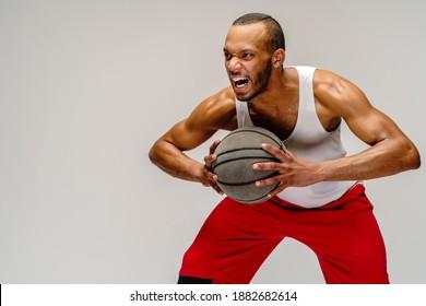 Muskulär afrikanischer amerikanischer Sportler, der Basketball auf hellgrauem Hintergrund spielt