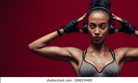 Muscular african female with headphones on red background. Fitness woman relaxing and listening music during her workout.