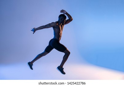 Muscular African-American shirtless man  leaping blue light.Studio shot