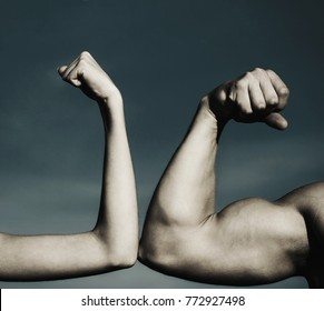 Muscular arm vs weak hand. Vs, fight hard. A heavily muscled man arm wrestling a puny weak man. Competition, strength comparison. Health concept. Hand, man arm, fist. Close-up. Black and white.
