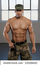 Muscular Army man in camouflage, no shirt with six pack abs