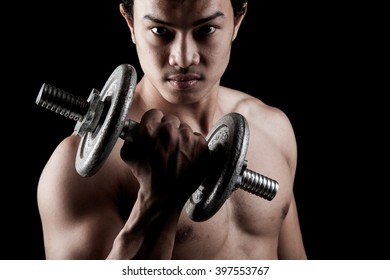 Muscular Asian man with dumbbell on dark background