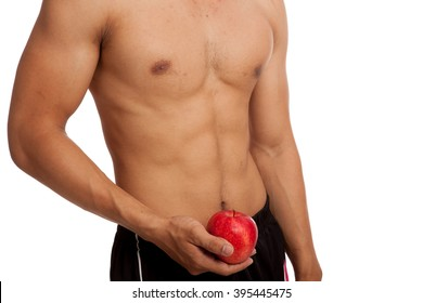 Muscular Asian man show six pack abs with red apple  isolated on white background