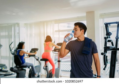 muscular asian young handsome man with towel drinking water while resting after workout for good healthy in fitness gym with woman, bodybuilder, healthy lifestyle, exercise and sport training concept