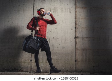Muscular athetic man wearing sportswear and carrying a gym bag, listening to the music and drinking water after a hard workout