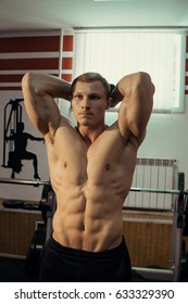 Muscular athlete, bodybuilder posing with muscles in the gym.