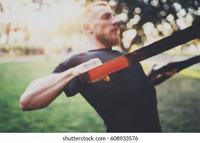 Muscular athlete exercising push up outside in sunny park at the morning.Attractive fittness man doing TRX exercises outdoors.Blurred background.
