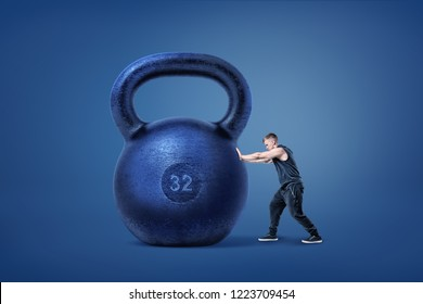 A muscular athlete ties to push and move from its place a huge iron kettlebell. Uneven conditions. Impossible task. Too heavy to move.