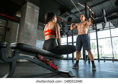 A muscular athletes doing workout at the gym. Gymnastics, training, fitness workout flexibility. Active and healthy lifestyle, youth, bodybuilding. Doing exercises with barbell, training upper body.