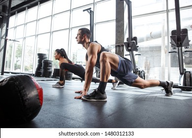 A muscular athletes doing workout at the gym. Gymnastics, training, fitness workout flexibility. Active and healthy lifestyle, youth, bodybuilding. Training in lunges and stretching exercises.