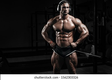 Muscular athletic bodybuilder fitness model training and posing with barbell in gym. Concept sport photo of exercises in gym