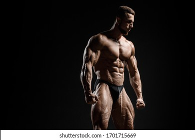 Muscular athletic bodybuilder fitness model posing. Isolated on black. Sport photo with dramatic light