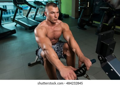 Muscular Athletic Bodybuilder Fitness Model Doing Heavy Weight Exercise For Back On Machine
