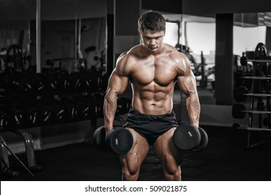 Muscular athletic bodybuilder fitness model posing with dumbbells after exercises in gym