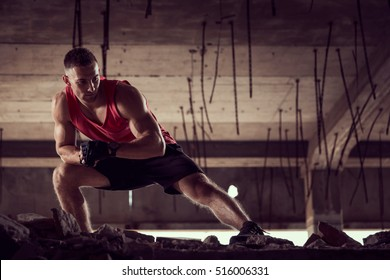 Muscular, athletic built, young man stretching out in a ruin building before workout