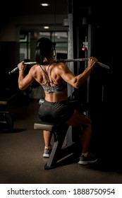 Muscular athletic female bodybuilder in black shorts pulled on sports simulator. Back muscles are very tense.
