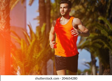 Muscular athletic man running on the jogging track on the palm trees background, male runner on the evening jog, fitness and healthy lifestyle concept