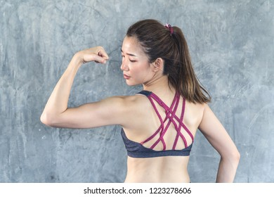 Muscular athletic woman in sports bra flexing her arm muscles with polished concrete wall background.