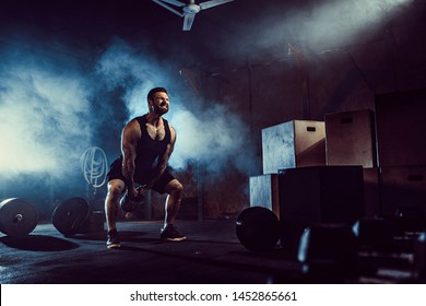 Muscular attractive caucasian bearded tasttoed man lifting kettlebell in a gym. Weight plates, dumbbell and tires in smoke background.