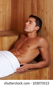 Muscular attractive man relaxing in a sauna