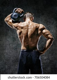 Muscular back of man. Rear view of fitness model with kettlebell on dark background. Strength and motivation