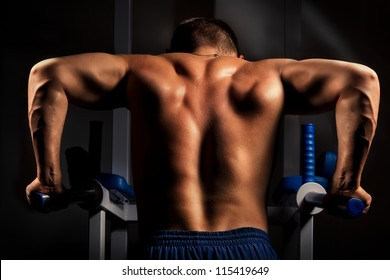 Muscular back of young bodybuilder training in dark background