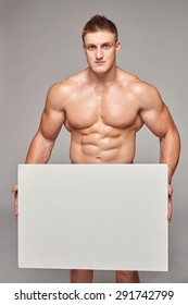 Muscular bare-chested male holding white banner placard with copy space