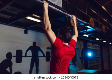 Muscular bearded male doing exercises on horizontal bar in a gym club.