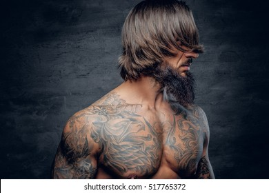 Muscular bearded male with tattooed body isolated with illumination on grey background.