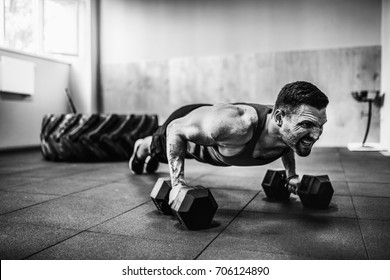 Muscular bearded man doing pushup exercise with dumbbell