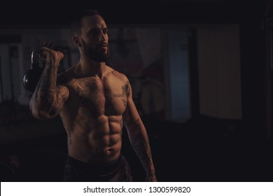 Muscular bearded man resting with kettle bell in hand