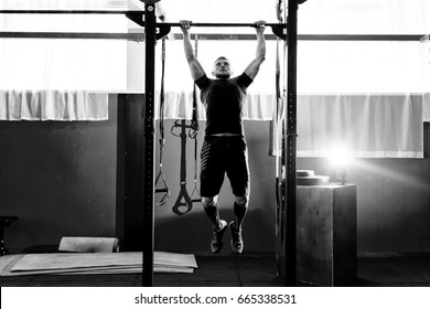 Muscular bearded man training his biceps and back in gym. Pull-ups. Workout lifestyle concept