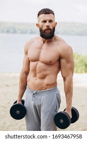 Muscular and bearded mustachioed man doing exercises with dumbbells outdoors. Bodybuilding and outdoor sports concept