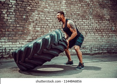 Muscular bearded tattooed fitness man moving large tire in street gym. Concept lifting, workout training.