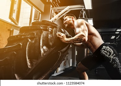 Muscular bearded tattooed fitness shirtless man moving large tire in gym. Concept lifting, workout cross fit training.