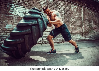 Muscular bearded tattooed fitness shirtless man moving large tire in street gym. Concept lifting, workout training.