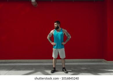 Tatooed man on the bedstead alone