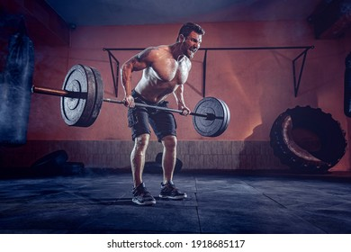 Muscular beardedman working out in gym doing exercises, strong male naked torso abs.