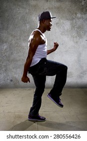 Muscular black man posing hip hop dance choreography on concrete background.  He is dancing in an urban setting.