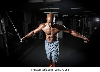 Muscular body builder working out at the gym on a cable machine.