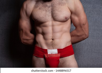 The muscular body of a man in the groin bandage. A red bandage is put on the man, on a gray background.