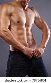 muscular body of young man in jeans. Shot in studio.